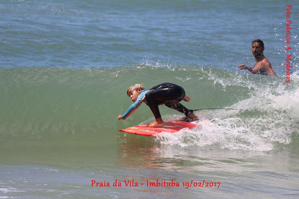 Guilherme se preparando para entrar em um tubo na Praia da Vila, com o pai, Tunico, atento, ao fundo