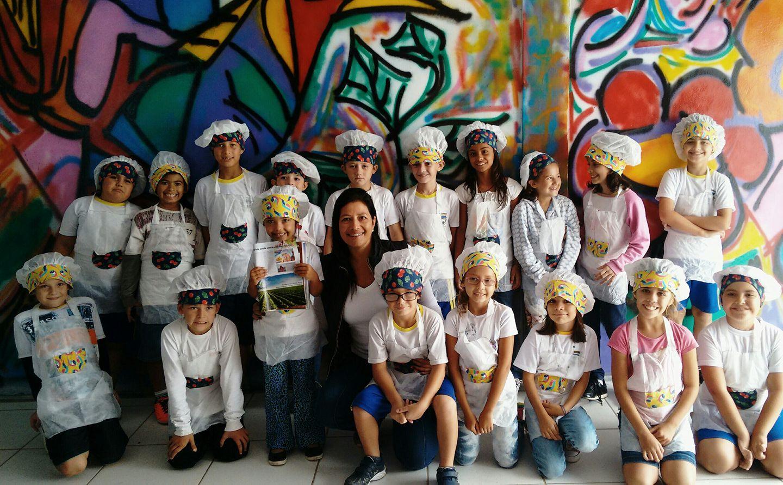 Professora Patrícia posa com pupilos no corredor da Escola, cujas paredes perderam os tons sombrios e ganharam cores com pinturas de alunos